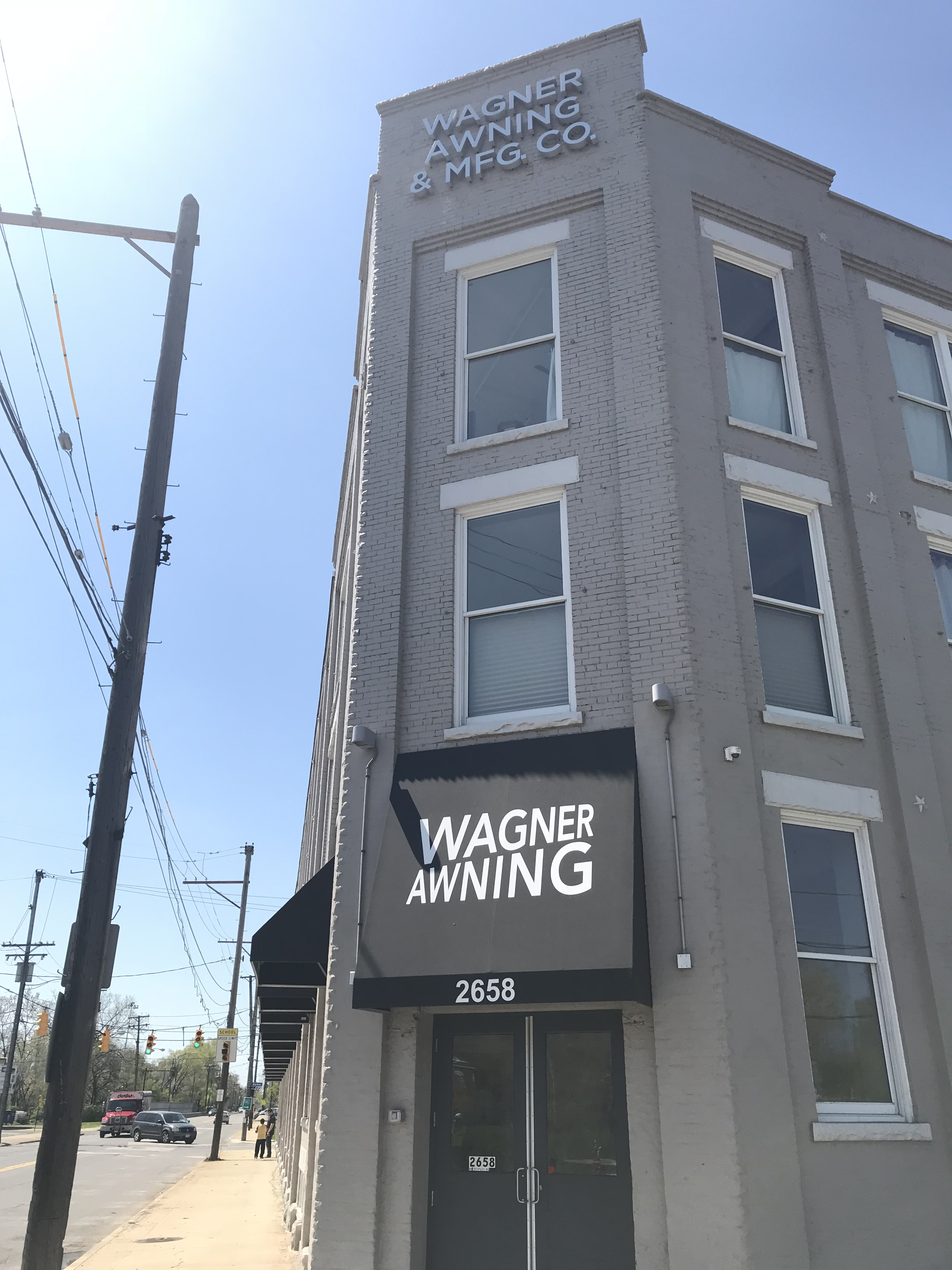 Gray brick building on street corner and entrance with awning that says Wagner Awning