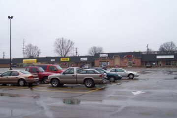 Shopping plaza with a variety of shops and cars in the parking lot