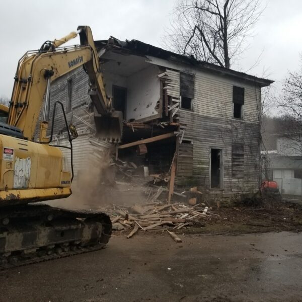 Large track hoe excavator tearing down an old building