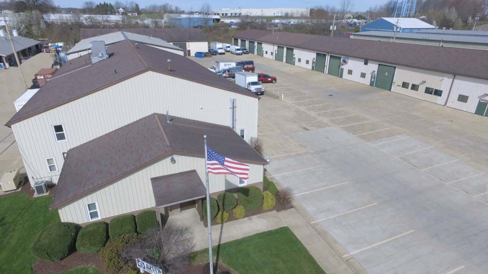Aerial view of a tan building with brown roof, flagpole flying an American flag, and a parking lot with a few vehicles parked in the back