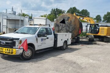 Ford F-350 Dually excavation utility truck pulling a large underground storage tank on a trailer