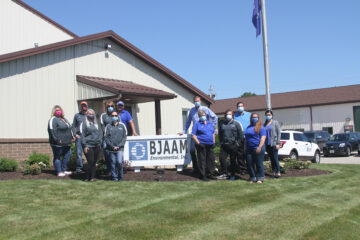 BJAAM Finance Team standing by the BJAAM sign outside the corporate headquarters on a sunny day