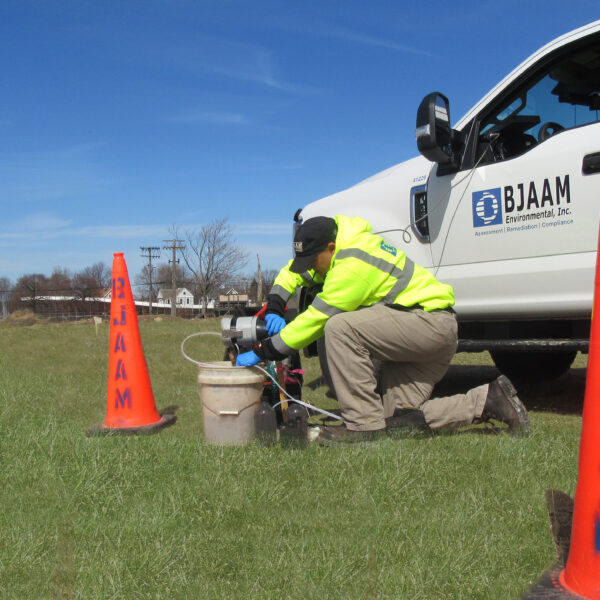 BJAAM employee kneeling on the ground performing ground water sampling next to a white BJAAM pickup truck and orange BJAAM safety cones set out in the area