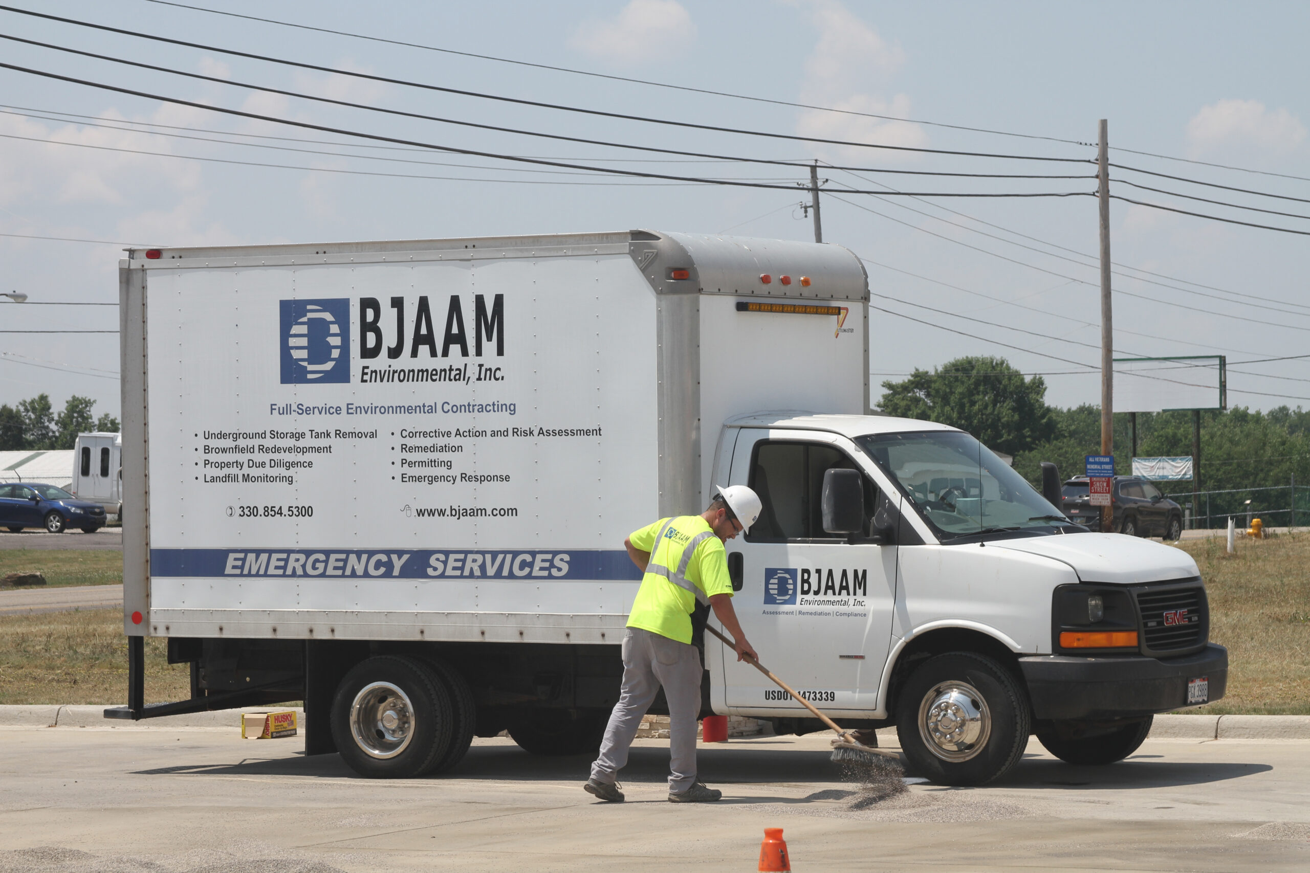 BJAAM employee sweeping in front of the company's Emergency Services truck.