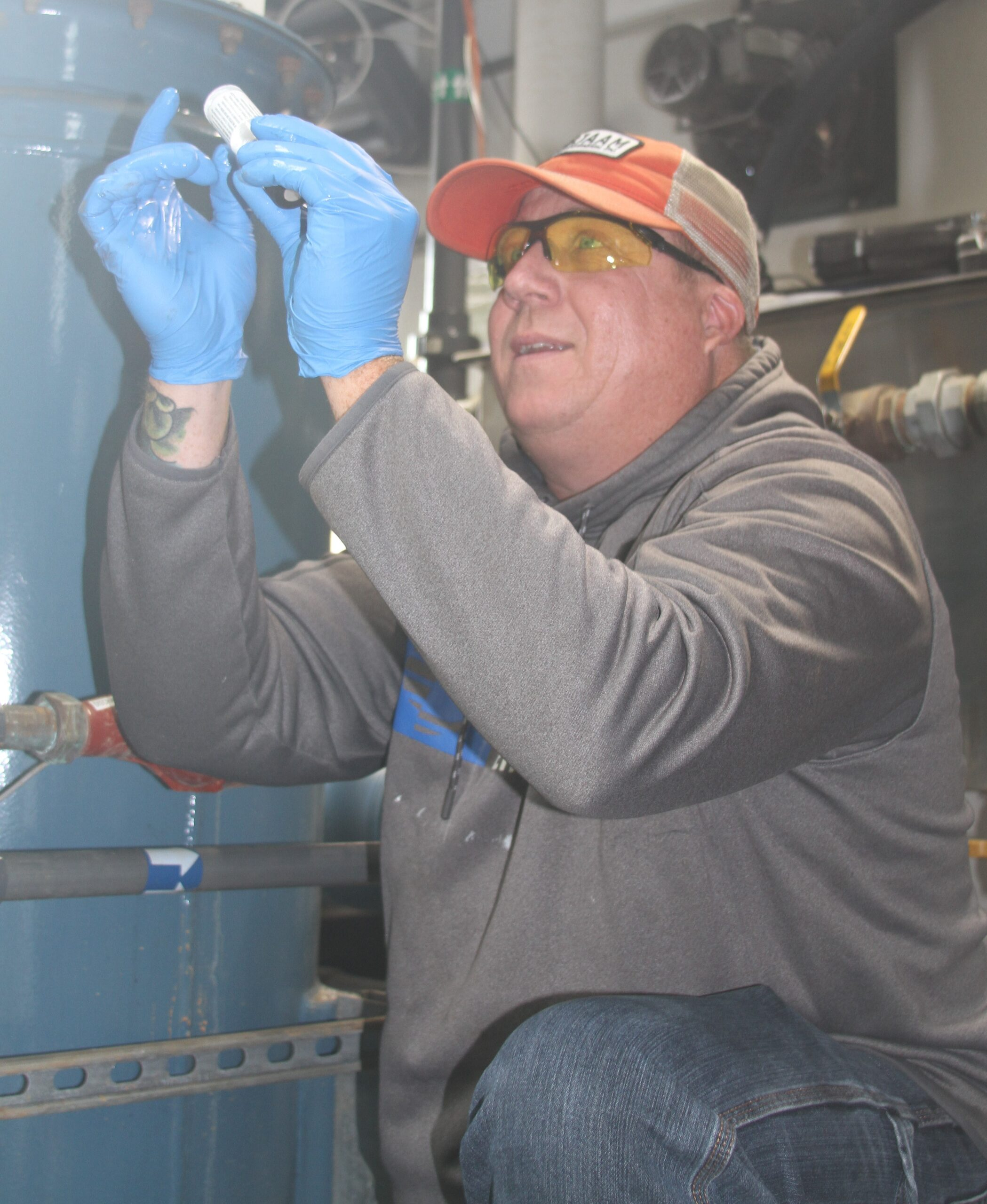 BJAAM employee wearing blue nitrile gloves and making sure there are no water bubbles in a water sample in a small vial