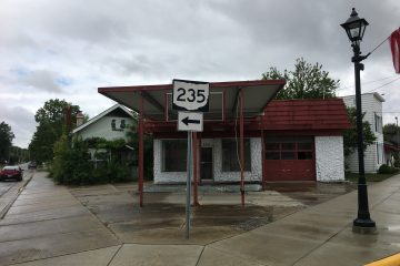 Abandoned gas station and canopy on a street corner on an overcast day