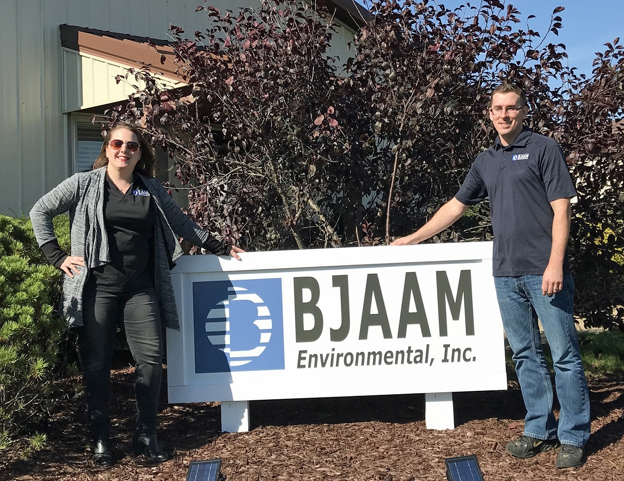 Lauren Goff and Clifton Wheeler standing on either side the the BJAAM sign in front of the corporate office building
