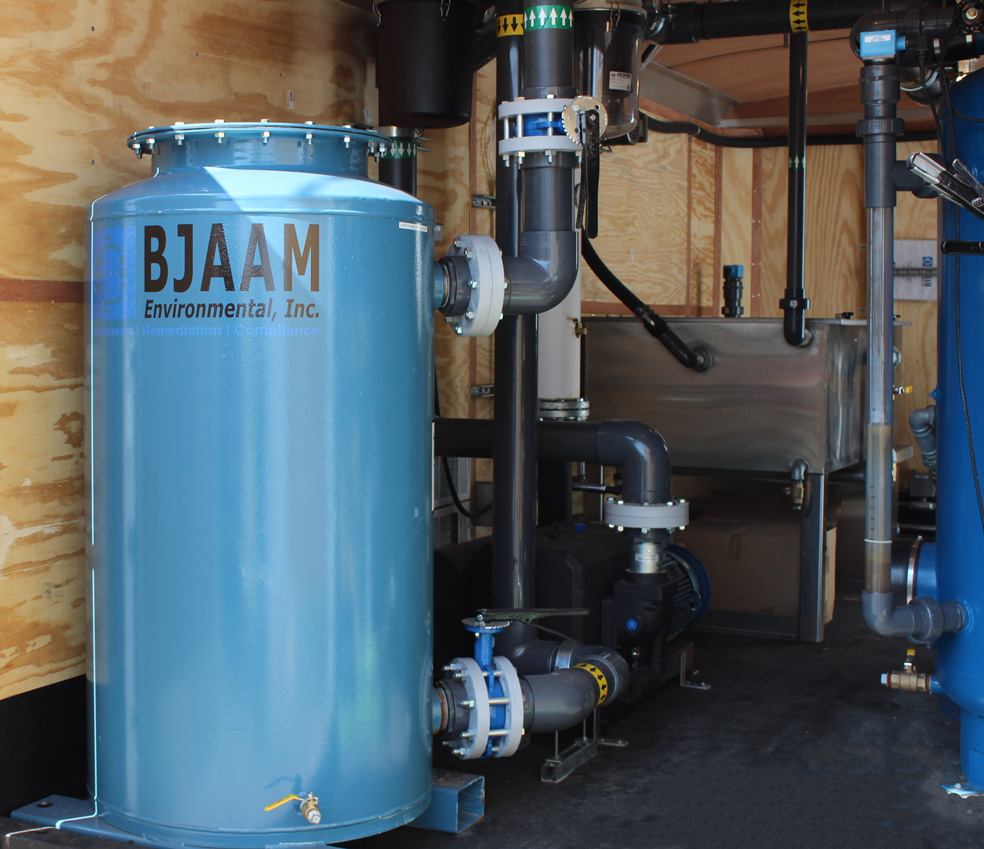 Blue cylindrical metal container with BJAAM logo that is connected to two gray pipes inside of a trailer